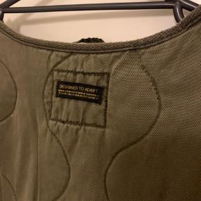 Army lidt oversize utility jakke i XL fra UO Ydre er bomuld og let foer r poly og med to sidelommer. Længde ca 78-79 cm Bredde fra ærmegab til ærmegab ca 67-68  Ærmer fra armhule og ned ca 50 Fra lav skuldersøm og ned ca 60 cm Ydre bomuld og tyndere foer poly - se vrang billede Sælges for ca 350 plus porto Har også en ekstra ubrugt i M og L - annoncer fælger!