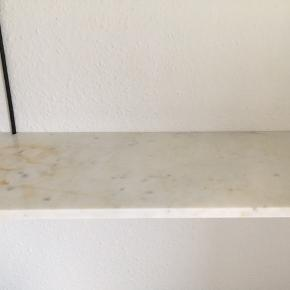 Marmor hylde med pulverlakeret hyldeknægte i rustfri stål. En enkelt skønhedsskade på selve pladen som ikke ses ved brug. Mål 24,5 x 70 cm