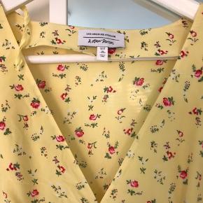 Lysegul sommerkjole med v-udskæring og mønster af små, fine blomster fra Other Stories Los Angeles Atelier. 100% silke med foret nederdel. Sidder pænt og passer både en str. 38 og 40. Ret regulær medium. Aldrig brugt.