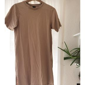 Beige / camel t shirt kjole fra Gina Tricot.  Har korte slidser i siderne.