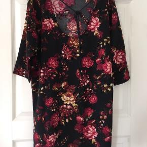 Super flot kjole med røde blomster.  Bagpå er lidt udskæring med bindebånd. Pasform er løs/oversize med 3/4 ærmer.  Kan sendes på købers regning eller medbringes til Østjylland/Fyn