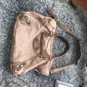 """Sælger min Balenciaga taske i City modellen. Den er fra 2006. Har kvittering og spejl. Tasken kunne se pænere ud, men det er ikke noget der som sådan ses når man går med den. Der kan være en Macbook 13"""" i. Den sælges billigt, så byd! Kan sendes eller hentes i 4534 Hørve"""