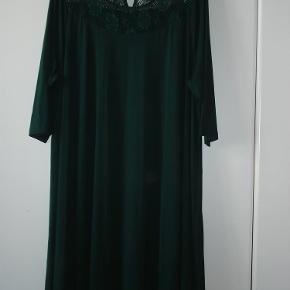 Varetype: Kjole fra Gozzip. Flaskegrøn med blondeindsats Farve: Flaskegrøn Oprindelig købspris: 600 kr.  Smuk, rummelig kjole fra Gozzip i størrelse 50. Klædelig, flaskegrøn kjole med blondeindsats foran ved halsen og bag på, hvor der er er lille kighul, der lukkes med en lille knap. 95% Viscose 5% Elastan På billederne kan man se gennem blonden på forstykket lige igennem til bagstykket med det lille kighul. Det kan fremstå lidt forvirrende på billedet. Der er godt med vidde i kjolen, der falder tungt og flot. Brystvidden er 135 cm. Længden, målt fra skuldersømmen er 98 cm. Kjolen er brugt én gang og fremstår ny. BYTTER IKKE!