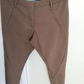 Størrelse 27, model Angelie. Farven er mere nude end fersken. Mangler en knap i linningen og kræver lidt syning da de er gået lidt op i sømmene nederst på bukserne.