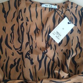 Ny bluse, str 38 med lange stropper til at slåom taljen. Selve blusen er lukket og kan strammes ind med stropperne  Mp 250