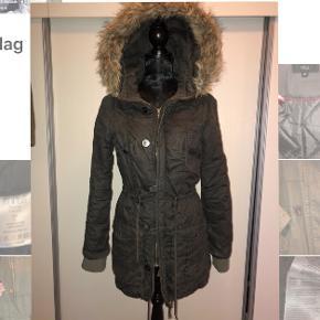 """Varm vinterjakke med justerbar snor i taljen, lynlås og knapper, bryst- og hoftelommer, hætte med """"pels"""" og tætsluttende ærmer.100% bomuld + tåler maskinvask. Ingen huller eller pletter. Kan afhentes i Århus eller 8752 Østbirk."""