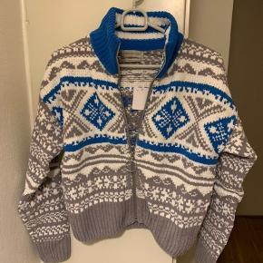Kort sweater cardigan (blå, grå, hvid) fra UO i str. XS (Passes nok også af mindre S - se mål) Mål: Længde ca 49 cm Bredde fra ærmegab til ærmegab ca 49 cm uden at stretche. Ærmer fra lav skulderkant og ned ca 49 cm Materiale kraftigt strik i poly. Har den også i S - se anden annonce ift mål! (Har selv en i brug, som jeg har vasket i vaskemaskine uden problemer) Nypris i UO 700 + og købt i år! Sælges for under halv pris plus porto. (375 inkl med DAO, såfremt MobilePay)