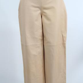 De flotteste og blødeste skind / læder bukser fra COS i farven NUDE / svag rosa. Med lynlås i siden og ellers helt enkle og uden detaljer. Med lige ben / brede ben / flare.  str. 38.