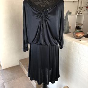 Super flot kjole fra C'N'C i lækker  polyesterkvalitet, med iøjnefaldende detaljer, kun brugt 2 gange. Flagermusærmer som er åben med slidse fra skulder til ærmemanchet. Stoffet ved halsen er i silke med sorte sten rundt i halsåbning. Der ligeledes små sten rundt forneden. Meget lækker at have på. Italiensk str. 26/40 svarer til xs men kan også passe  en S/M. Længde ca. 86 cm.  Sender med GLS eller DAO, køber betaler forsendelse på 35 Kr. Betaling via TS eller MobilePay.