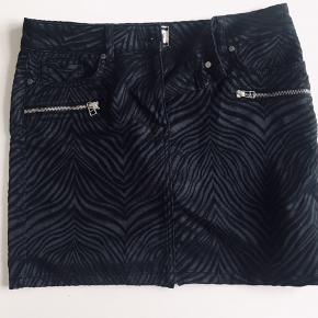 """Sort og cool sort nederdel i """"zebravævet"""" stof. Jeanslommer foran og bag på. Almindelig i størrelsen.  Længde: 39 cm Livvidde: 2 x 39  Se også mine andre annoncer og gør et godt køb 🎶"""