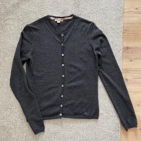 Cardigan fra Burberry i 100% uld / merino. Farven er mørk grå / antracit. Lukkes men knapper, og har flotte detaljer i den klassiske Burberry-tern. Størrelse M. Fremstår som ny.  Søgeord: strik, sweater, knit, wool