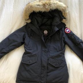 Varetype: Frakke Farve: Marineblå Oprindelig købspris: 5000 kr.  Sælger min canada goose jakke. Den fejler intet. Hætten kan lynes af. De originale skilte sidder stadig på jakken (lynlås, og indeni)! Giv gerne et bud. Den er super varm!  PS. Der er en lys plet på vestre arm og hætten (det på hætten kan ikke ses så længe pelsen er på.