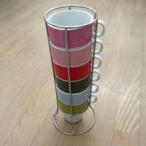 Kaffekopper i stativ brugt til pynt så ingen skår eller ridser. Der er dog en lille bitte skræmme øverst i kanten i den pink maling på pink kop som man kan ane på billede 4