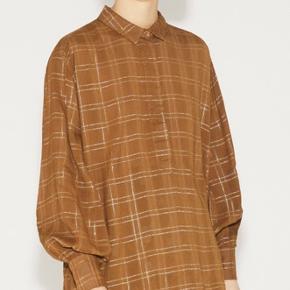 DELUSIONARY TOP, CARAMEL  Lang skjorte i viskose med elegante lurex-tern, lille krave og lange ærmer. Et klassisk snit som passer ind i enhver garderobe. De diskrete metalliske tern er en smuk detalje på skjorten, som gør det overflødigt at tilsætte smykker. Fås i navy og camel. Stylen kan krympe let ved vask. Modellen er 177 cm høj og har en str. 36 på. Stylen måler 124 cm rundt om brystet, 72,5 cm i længden og 83,5 cm i armlængden.