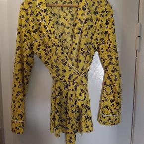 Gul blomstret skjorte med knap og bindebånd i livet.