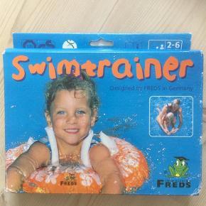 """Brand: Freds Varetype: Børn udstyr Størrelse: 2 Farve: Se billede Oprindelig købspris: 249 kr.   Svømmetræner fra """"Freds Swim Academy's"""" svømmeskole. Størrelse: 2-6 år (15-30 kg)  Børn sutter meget på deres badering og det er en """"badering"""" uden phalater.  Svømmetræneren er med til gøre børn fortrolige og trygge ved vandet. Svømmetræneren giver børnene mulighed for at bevæge sig frit i vandet i en naturlig svømmeposition.  Swimtrainer Classic er designet i Freds Swim Academy's svømmeskole. Den er fremstillet med henblik på """"sikker sjov"""" i vandet.  Sammen med svømmetræneren følger manual  Børnene kan ikke glide ud af svømmetræneren og svømmetræneren kan ikke tippe."""