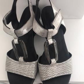 Smukke sølvfarvede sandaler i læder med benspænde. Hæl 7 cm.  Næsten ikke brugt. Fremstår uden mærker og skader.  Fast pris ex levering Ingen bytte
