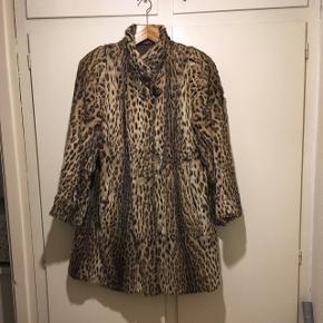 Vintage pelsfrakke med skulderpuder, A-form og meget fine detaljer. Frakken er ret slidt, men stadig blød og varm og i et klassisk elegant design med stumpeærmer. Meget mrs. Maisel. Passer small og medium og en kort large.