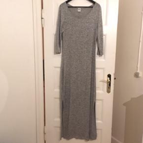 Lang, lysegrå kjole med slidser i siden. Str. L. Behagelig med meget stræk, og den falder tungt og flot. 150cm lang.