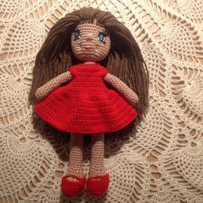 Hjemmehæklet dukke med kjole og sko. Dukken måler 26 cm og er hæklet i 100 % bomuld, på nær håret, som er akryl. Dukken kan vaskes på 40 grader. Der er ingen løse dele, som børn kan få galt i halsen, da øjne, næse og mund er syet på.  Der kan tilkøbes flere kjoler i andre farver. Sender med dao på købers regning.