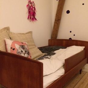 Superfin retro seng i teaktræ. Det er en afkortet voksenseng og har nu målene 82x140 (bredde målt ved sengehest). Påsat sengehest i begge sider. Med fjederbund. Sælges uden madras.