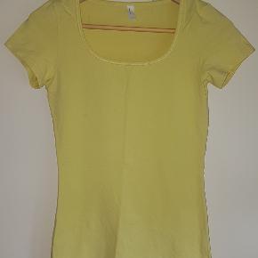 Lækker gul t-shirt i en bomuldslykra-miks, der giver den en skøn pasform og lidt ekstra stretch.