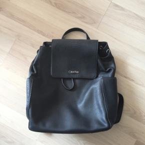 SOLGT!  Calvin Klein rygsæk i sort med slangskind-look. 300 + fragt. ;-)  Den måler ca. 36H x 39L.