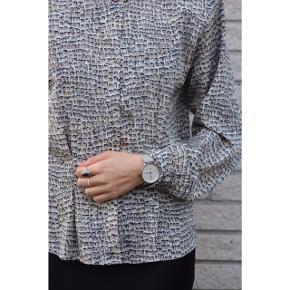 Formsyet blank silkeskjorte i hvid og blå. Skjorten er som ny, og fejler intet. Knapperne er skjulte, hvilket giver et meget elegant look. Skjorten kan kombineres til alt, og vil især klæde jeans. Ethvert klædeskab vil blive beriget af denne sag. Passer en størrelse 32-38. Skriv en privat besked for mere info🌸 Pris: 200kr.