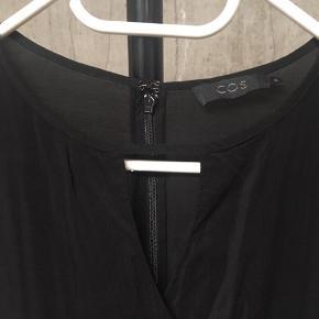 Smuk og enkel sort kjole fra COS med slå-om detalje.  Brugt 1 gang og fremstår derfor i perfekt stand.