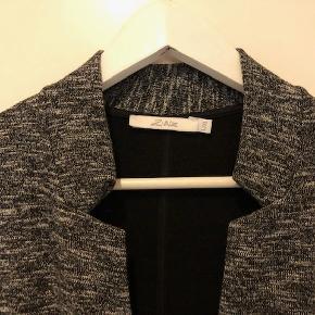 Lækker jakke/cardigan fra 2biz. Den er i sortmeleret strækstof og lukkes med knappe foran.  Byd :-)