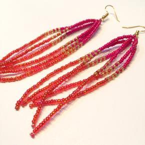 Øreringe fra Walina  Lange orange røde guld og pink glas perler på gyldne øreringe.  Perle-vedhænget måler 9,5 cm.  Jeg kan handle med mobilpay: Jeg sender gerne med post nord til din postkasse (+10 kr 5 dages leveringstid eller 29 kr 1 dags leveringstid), hvis du ikke kigger forbi og henter dem. Jeg kan handle via Trendsales med DAO pakkepost (+32 kr), hvor du afhenter pakken ved ønsket DAO udleveringssted.  mvh Lise