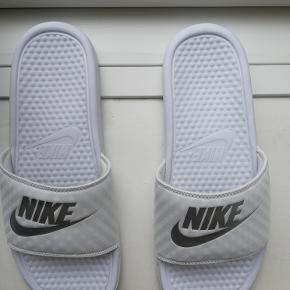 Sandaler, str. 42, Nike , Hvid , Syntetisk, Næsten som ny Hvide/sølvmetallic Nike sliders/badesandaler. Unisex. De er brugt en enkelt gang indendøre, men jeg har desværre købt dem for store. De er ellers normale i størrelsen. Størrelsen hedder: EU: 42, UK: 7,5, Længde 27 cm. Det sidste billede er fra nettet. Købspris: 250. Eventuel fragt lægges oveni. Kan også afhentes på Frederiksberg