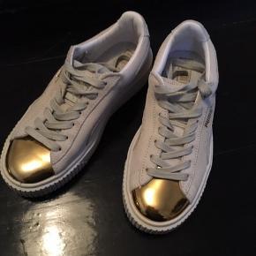 Helt ny sko fra PUma i hvid ruskind med guld på tåen.