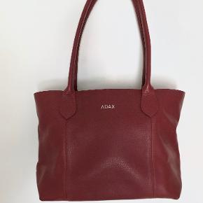 Yderst smuk taske fra Adax i perfekt, lavet af 100% ægte kvalitetslæder. Den har aldrig været brugt og fremstår som ny. Der medfølger også en original pose fra Adax til tasken. Nypris var omkring 1.000kr.  Prisen er til forhandling ved hurtig handel. Sender gerne.