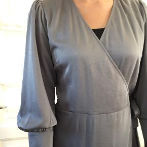 Dueblå slå-om-kjole i 100% polyester. Købt sidste år, men har aldrig fået den brugt. Giv gerne et realistisk bud.