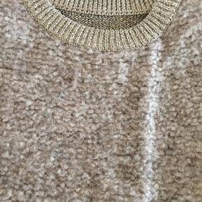 """Varetype: Smuk strikbluse Farve: Beige Prisen angivet er inklusiv forsendelse.  Virkelig smuk strik fra By Malene Birger med """"guld"""" ærmer og ryg.  Længde 57 cm.  Prisen er fast, da den fremstår som næsten ny."""