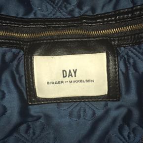 Fin, mørkeblå Day by Birger et Mikkelsen weekendtaske med guldlynlås. Brugt, men i rigtig god stand. Udgaven er med fór og indbroderede blomster. Indeni er det store rum og en mindre lomme.