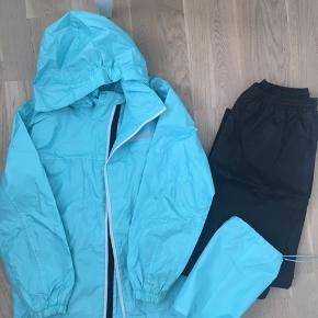 Pænt regnsæt fra Stadium i str. 146/152 i turkis jakke og sorte bukser. Der medfølger en opbevaringspose. Regntøjet er brugt max 3 gange og har enkelte små brugsspor.