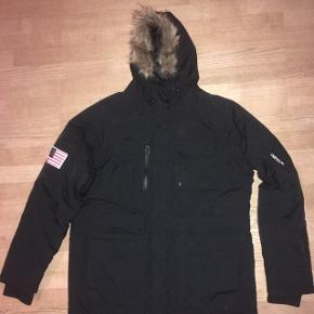 Lækker sort herre parka jacket fra Vertical model Aspen M str. 2XL med hætte med pelskant på. Brugt få gange. Fra røgfrit hjem.