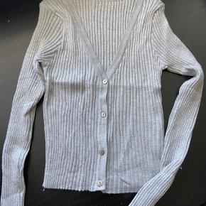 Cropped sweater/cardigan i grå. Den er tætsiddende og har meget stræk i.