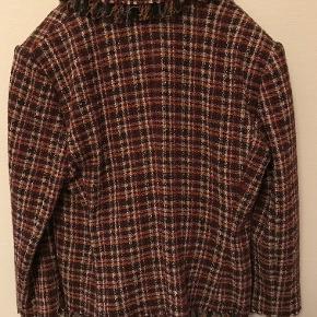 Ternet kort jakke i str. 44 (fransk størrelse). Der er frynser på ærmer, krave og kanten forneden på jakken. To små lommer. Har aldrig været i brug.