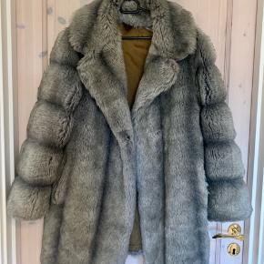 """Super lækker frakke i faux fur - til den dyrerettighedsbevidste. ;)  Købt som et """"håndværkertilbud"""", da den er gået op i foret indvendigt - dette kan sagtens sys! Derudover fejler den intet, og ser i virkeligheden meget ægte ud.  Sælges udelukkende fordi jeg har for mange jakker. 🌸"""