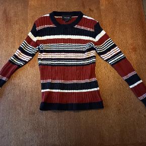 Fin tætsiddende crop sweater med trekvartærmer i flotte efterårs/vinter nuancer.