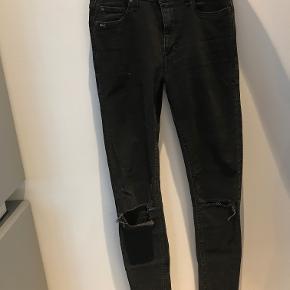 Smarte jeans fra Tiger of Sweden med huller ved knæerne str. 26/32 i skinny model.  Ny pris: 1200kr. Nu: 350kr. eller BYD