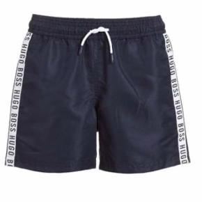 """Sporty BOSS shorts i navy polyester i en glatvævet kvalitet med en flot, ternet vævning. Ned langs buksebenene er der en hvid stribe med navnet """"Hugo Boss"""" i hvid. Bagpå er der hen over lænden en smal, hvid stribe, og fortil er der et hvidt bindebånd med navy ender. Aldrig brugt, men dog vasket en gang efter anvisningen. Str er xs -12 år, men dog lidt små i str. De passer en str. 9-12 år. Nypris 600 kr, mp 350 kr."""