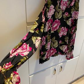 Bluse med puf ærmer og flotte pinke blomster.