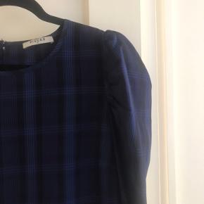 Fin mørkeblå og sort ternet bluse med pufærmer. Lukkes bagpå med en lille knap. Brugt få gange.