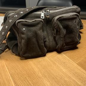 Nunoo taske i grå, ruskind. 100% kalveskind. Kan bruges både som skuldertaske eller crossover taske - justerbar strop medfølger. Mål: L: 34 x H: 19 x D: 10 cm Har lidt slidspor ved lynlåsen, som ses på billedet.