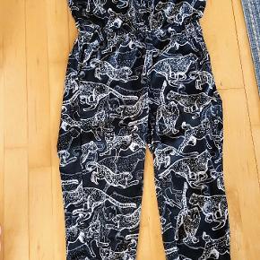 Skøn jumpsuit, med leopard mønster, det er en str M eller 38, lille 40. Dejlig afslappet stil, smal elastik i livet og skrålommer. 2 brystlommer og skjult knaplukning foran ved bryst god plads øverst, 55 cm over bryst  og skridtlængde ca 63 cm  krøller slet ikke, kan rulles sammen i kufferten og er lige så fin når du tager den op igen.. mrk er klippet af i nakken da det generede, men jeg mener 80 % at det er H&M :-)