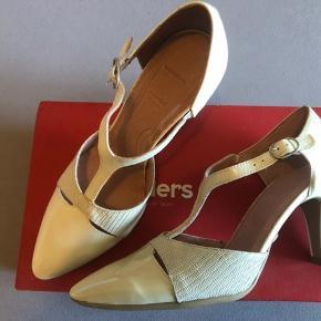 Fin sko i skind, men har desværre opdaget at de ikke er helt ens i farven på snuderne. Tænker ik man ser de i brug men det skal selvfølgelig nævnes.   Farven er creme med perlemor.  Derfor den lave pris.   Nye og ubrugte.
